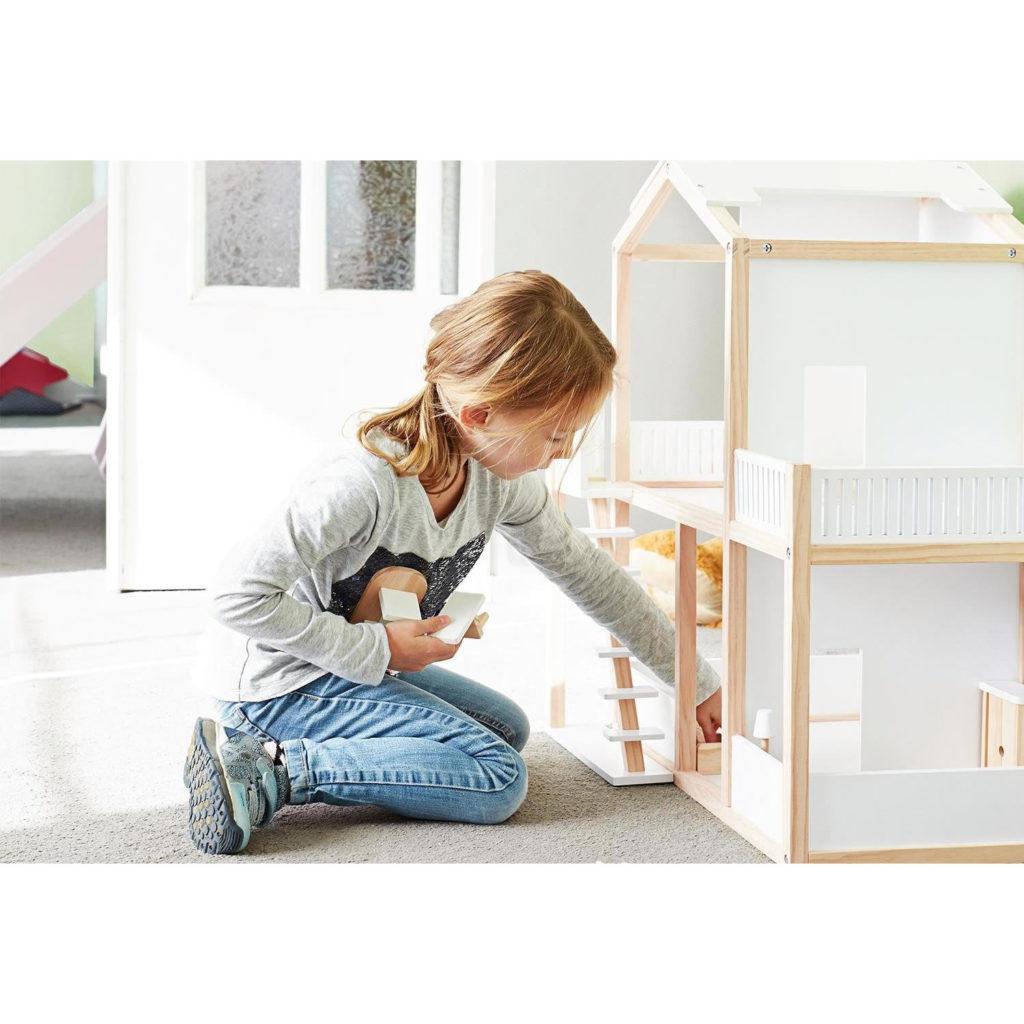 Kind spielt mit Puppenhaus